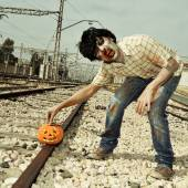 Zombie putting a carved pumpkin on the railroad tracks — Stock Photo