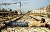 Zombie spaventoso schiacciando un pisolino presso i binari della ferrovia abbandonata — Foto Stock