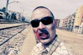 Scary zombie with sunglasses at abandoned railroad tracks, with  — Stockfoto