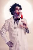 Un médico de zombie con una jeringa con sangre, con un efecto de filtro — Foto de Stock