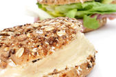 Brown bagel filled with cheese spread — Stock Photo