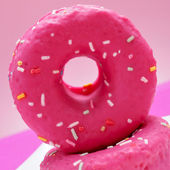 Donuts coated with a pink frosting and sprinkles of different co — Stock Photo