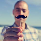 Young man with a fake moustache — Stock Photo