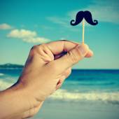 Man hand with a fake moustache on the beach, with a filter effec — Stock Photo