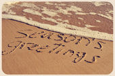 Seasons greetings on the beach, with a retro effect — Stock Photo
