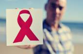 Young man with a picture of a red ribbon for the fight against A — Stock Photo