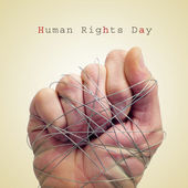 Man hand tied with wire and the text human rights day — Stock Photo