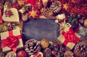 Gifts and christmas ornaments and a blank chalkboard — Stock Photo