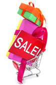 Gifts and a signboard with the word sale in a shopping cart — Stock Photo
