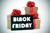 Gifts and a signboard with the text black friday — Stock Photo