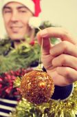 Young man covered with christmas ornaments — Stockfoto