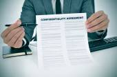 Young man showing a confidentiality agreement document — Stock Photo