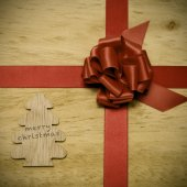 Merry christmas written in a wooden tree and a red ribbon bow — Stock Photo