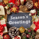 Text seasons greetings and gifts and christmas ornaments — Stock Photo