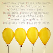 Golden balloons and the text happy new year in different languages — Stock Photo