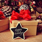 Gifts and text happy holidays in a star-shaped chalkboard — Stock Photo