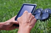 Man using a tablet computer in a park — Stock Photo