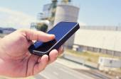 Man using a smartphone in an industrial park — Stock Photo