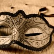 Carnival mask on a wooden surface in sepia toning — Stock Photo #63527401