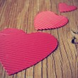 Red hearts on a rustic wooden surface — Stock Photo #63575423