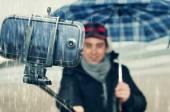 Jeune homme tenant un selfie sous la pluie — Photo