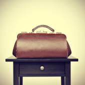 Old doctors bag on a table — Stock Photo