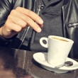Young man with an electronic cigarette and a cup of coffee in th — Stock Photo #66018775