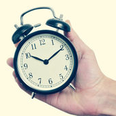 Man hand holding a mechanical alarm clock, with a retro effect — Stockfoto