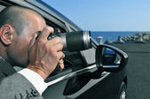 Detective or paparazzi taking photos from inside a car — Stock Photo