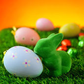 Easter rabbit and decorated eggs on the grass — Stock Photo