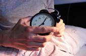 Young man in bed setting the alarm clock — Stock Photo