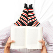 Young man reading a book in bed — Stock Photo