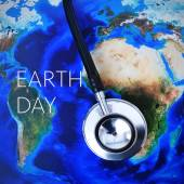 Stethoscope on a world map (furnished by NASA) and the text eart — Stock Photo