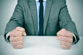 Man in suit banging his fists on a desk — Stock Photo
