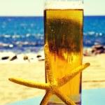 Starfish and refreshing beer on the beach — Stock Photo #74360845