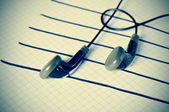 Earphones on a staff simulating musical notes — Stock Photo