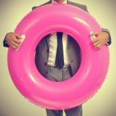 Businessman with a pink swim ring, with a retro effect — Stock Photo