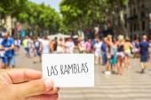 Man shows a signboard with the text Las Ramblas, at Las Ramblas — Stock Photo