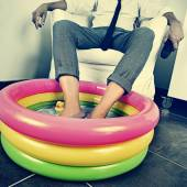 Man in suit soaking his feet in an inflatable water pool — Stock Photo