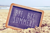 Text bye, bye summer in a chalkboard on the beach — Stock Photo