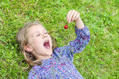 Girl lying on the grass with cherry — Stock Photo