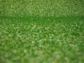Green artificial synthetic grass meadow background — Zdjęcie stockowe