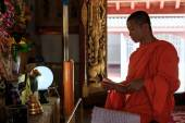 Young Buddhist Monk light incense sticks — Stockfoto
