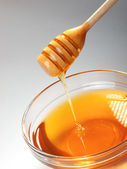 Honey in glass bowl with dipper — Stock Photo