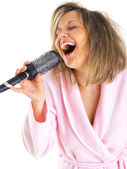 Woman in housecoat singing with hairbrush — 图库照片