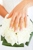 Bride's hand over roses — Stock Photo