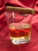 Whiskey and cigar on red satin — Photo