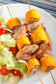 Chicken wings with corn skewers — Stock Photo