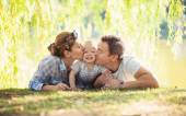 Happy parents kissing toddler boy. Father, mother and son relaxing on the lawn. — Stock Photo