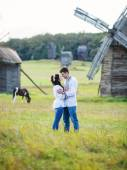 Young couple on the field, some of the old mills — Stock Photo